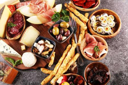 Juego de aperitivos de vino italiano antipasti. Variedad de queso, aceitunas mediterráneas, encurtidos, Prosciutto di Parma, tomates, anchoas y vino en vasos sobre fondo negro grunge