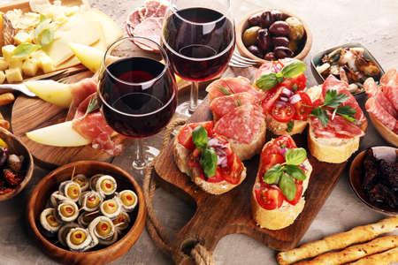 Italienische Antipasti-Wein-Snacks. Käsesorte, mediterrane Oliven, Gurken, Prosciutto di Parma, Tomaten, Sardellen und Wein in Gläsern auf schwarzem Grunge-Hintergrund