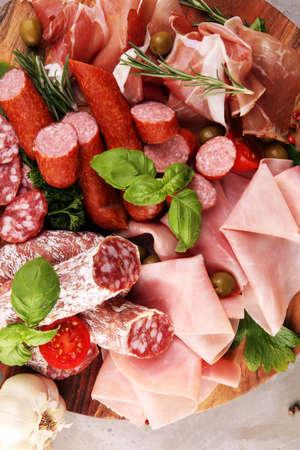 Plateau de nourriture avec de délicieux salami, morceaux de crudo de prosciutto tranché, saucisse et basilic. Plateau de viande avec sélection. Banque d'images