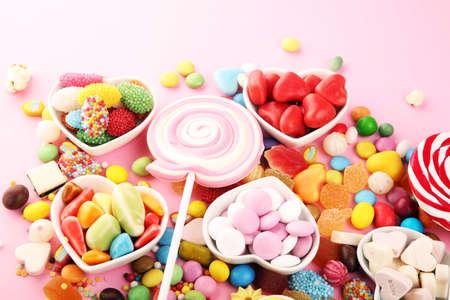 bonbons avec de la gelée et du sucre. gamme colorée de différents bonbons et friandises pour enfants sur rose