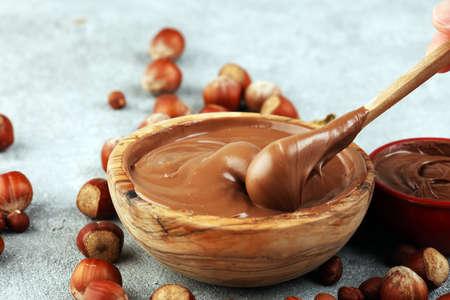 Crema di nocciole fatta in casa in ciotola di legno. Crema di torrone alla nocciola in tavola