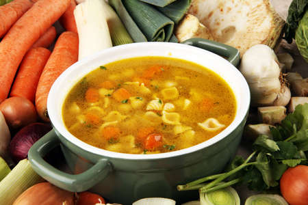 Broth with noodle and carrots, onions various fresh vegetables in a pot - colorful fresh clear spring soup. Rural kitchen scenery vegetarian bouillon or stock Фото со стока