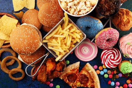 Ungesunde Produkte. Essen schlecht für Figur, Haut, Herz und Zähne. Auswahl an schnellen Kohlenhydraten mit Pommes und Cola Standard-Bild