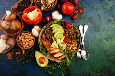 Healthy salad bowl with quinoa, tomatoes, chicken, avocado, lime and mixed greens, lettuce. Food and health. Stock Photo
