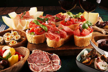 Italian antipasti wine snacks set. Cheese variety, Mediterranean olives, pickles, Prosciutto di Parma, tomatoes, anchovy and wine in glasses over black grunge background