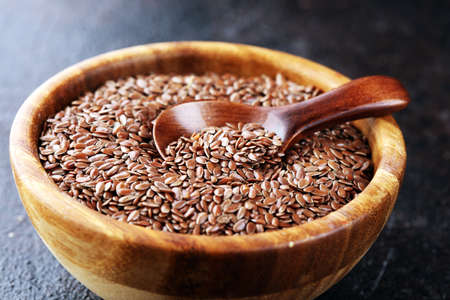 Uncooked linseed in wooden spoon, rustic style. linseed healthy food