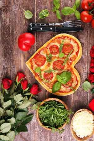pizza Heart shaped margherita with tomatoes and mozzarella vegetarian. Food concept of romantic love for Valentines Day. Reklamní fotografie - 137800596