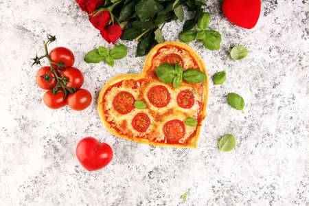 pizza Heart shaped margherita with tomatoes and mozzarella vegetarian. Food concept of romantic love for Valentines Day. Reklamní fotografie