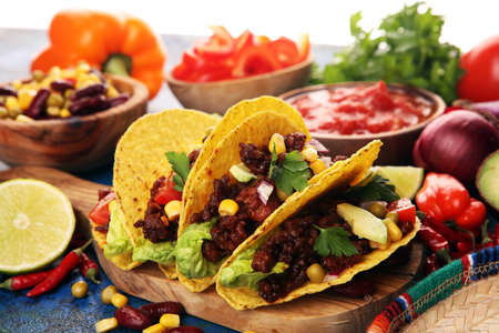 Mexican tacos with beef, tomatoes, avocado, chilli and onions