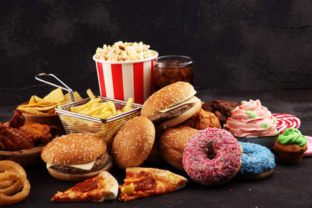 Unhealthy products. food bad for figure, skin, heart and teeth. Assortment of fast carbohydrates food with fries and cola Reklamní fotografie - 137800784