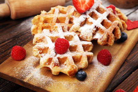 Traditional belgian waffles with fresh blueberries, sugar and raspberries on wood