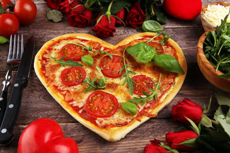 pizza Heart shaped margherita with tomatoes and mozzarella vegetarian. Food concept of romantic love for Valentines Day.