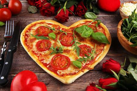 pizza Margherita a forma di cuore con pomodoro e mozzarella vegetariana. Concetto di cibo di amore romantico per San Valentino.