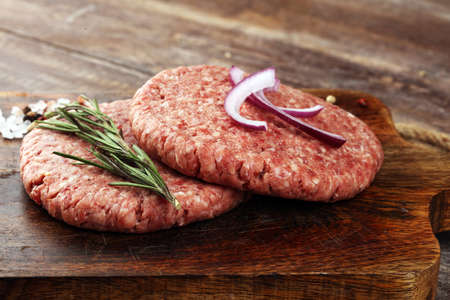 raw patty for angus burger on wooden cutting board with herb