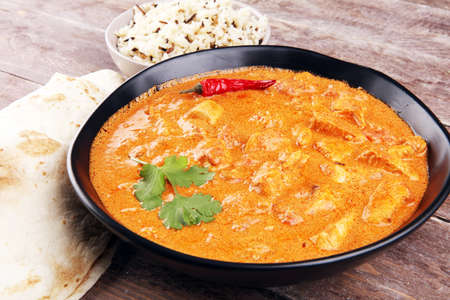 Chicken tikka masala spicy curry meat food in pot with rice and naan bread. Indian chicken tikka masala
