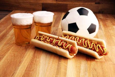 hot dogi z musztardą i keczupem na stole z piwem z beczki na piłkę nożną.