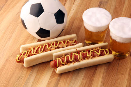 hot dogs with mustard and ketchup on the table with draft beer for football soccer party. Standard-Bild
