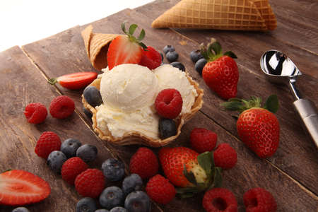 Vanilla ice cream scoops with fresh berries on table