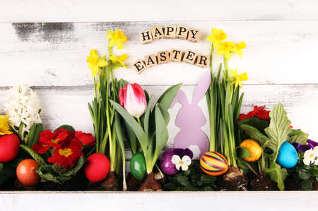 Happy Easter wooden letter. Holiday concept design. Happy Easter flat lay with flower and eggs in beatiful colors.