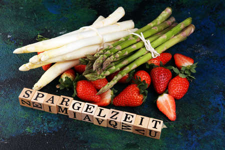 White and green fresh asparagus with a bunch of healthy strawberries with Spargelzeit wooden letter.  版權商用圖片