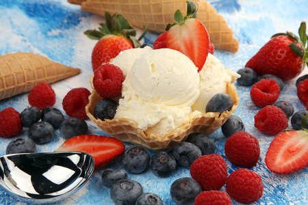 Vanilla ice cream scoops with fresh berries on table