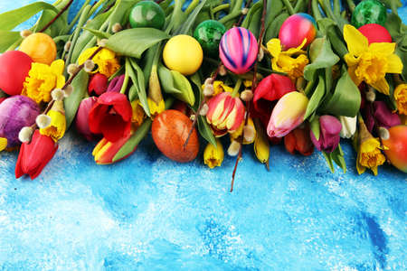 blooming daffodils and easter eggs for spring decoration on rustic background