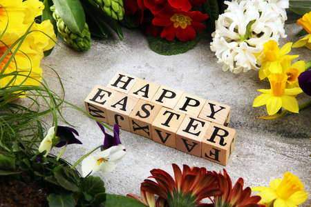Joyful colorful spring background for a Happy easter with seasonal greeting text with rustic letter with flowers and pussy willow cats