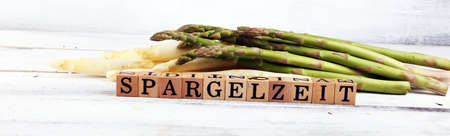 Healthy fresh White and green asparagus on vintage background with Spargelzeit wooden letter.