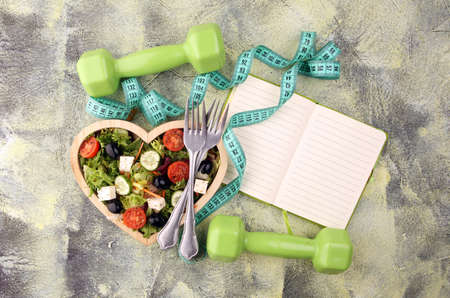Authentic fresh salad in a wooden heart shaped cup with dumbbells excercise equipment, measuring tape on table. healthy lifestyles, good health Concept with fresh ingredients 版權商用圖片