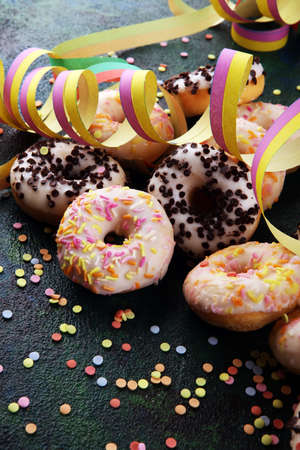 celebration donuts with colorful party streamers and confetti on rustic background 版權商用圖片