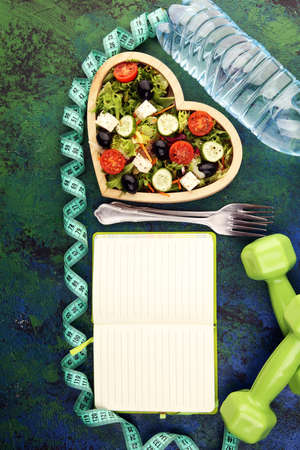 Authentic fresh salad in a wooden heart shaped cup with dumbbells excercise equipment, measuring tape on table. healthy lifestyles, good health Concept with fresh ingredients 写真素材