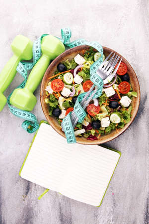 Authentic fresh salad in a stone cup with dumbbells excercise equipment, measuring tape and fork on table. healthy lifestyles, good health Concept.