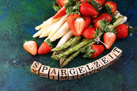 White and green fresh asparagus with a bunch of healthy strawberries with Spargelzeit wooden letter.  写真素材