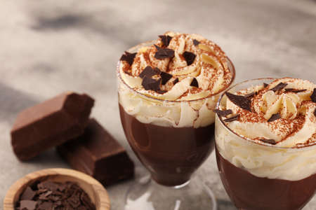 Hot chocolate cocoa with whipped cream on vintage background, selective focus