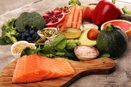 Healthy food clean eating selection: fish, fruit, vegetable, cereal, leaf vegetable on background Foto de archivo