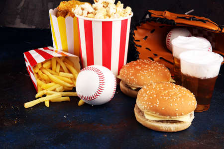 Popcorn and burger, fries and chicken nuggets on the table with draft beer. Baseball party food Banque d'images