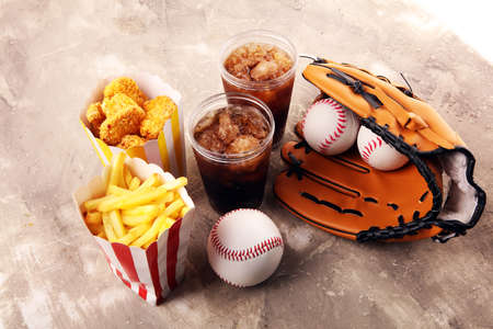 Chicken nuggets and french fries on the table with cola softdrink. Baseball party food
