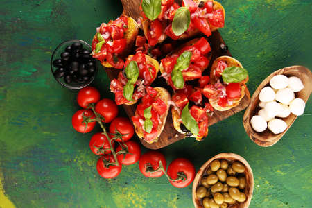 Bruschettas on cutting board on rustic background with tomatoes