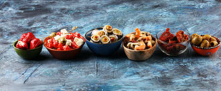 Antipasti Appetizer sweet cherry peppers stuffed with soft cheese feta, olives with oil. Seafood and anchovies with olives and dried tomatoes. Italian mediterrane Reklamní fotografie