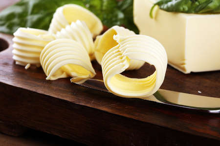 yellow block of fresh butter sliced on wooden cutting board and butter swirls. Slices of margarine or spread, fatty natural dairy product. High-calorie food for cooking