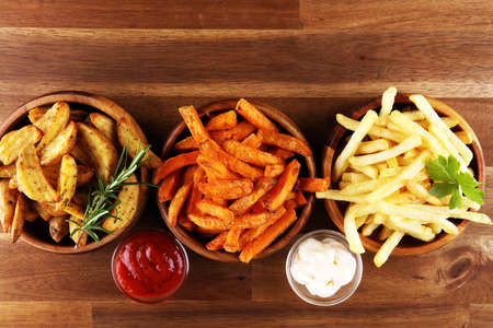 Variety of potatoes with fries. potato wedges, french fries, sweet potato for lunch on background