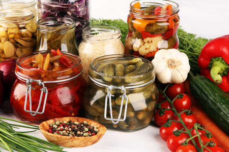 Preserves vegetables in glass jars. Pickled Cucumber, carrot, fermented cabbage and onions on rustic table
