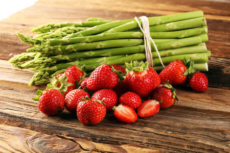 green fresh asparagus with a bunch of healthy strawberries