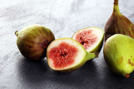 Fresh figs. Fruit with half and hole figs on background.