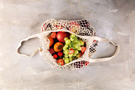 Fresh summer fruits in eco bag with apple, grapes, berries, plums and organic apricot.