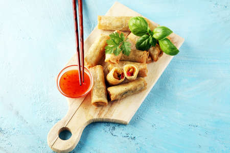 Fried chinese spring rolls with sweet chili sauce on background