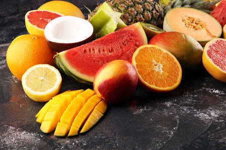 Tropical fruits background, many colorful ripe tropical fruits on rustic table Archivio Fotografico