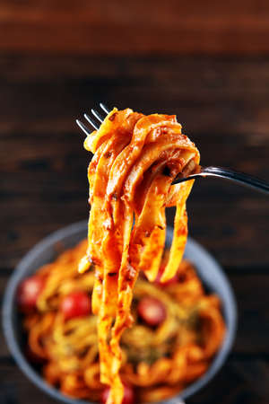 tagliatelle pasta with tomato sauce parmesan basil on rustic table Archivio Fotografico