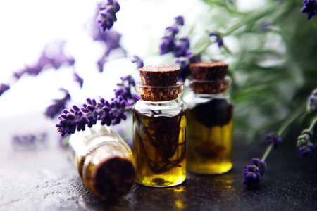 lavender oil in a glass bottle on a background of fresh flowers on table Archivio Fotografico