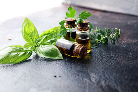 Fresh raw herbs from the garden and the different oils for massage and aromatherapy on table